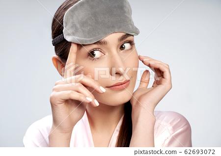 Beautiful young woman touching gray sleep mask 62693072