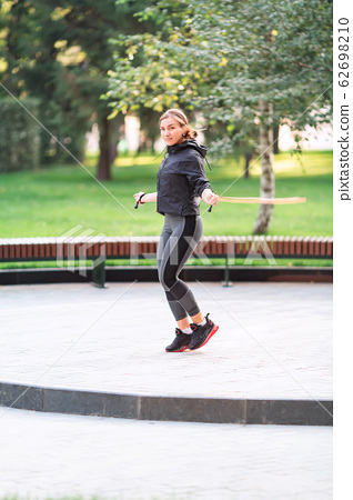 Fitness woman jumping on a rope outdoor in urban 62698210