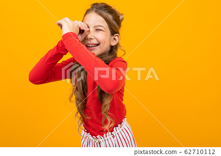 surprised girl with curly hair in a red blouse and striped trousers looks out for something on an 62710112