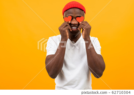 Smiling American dark-skinned man in a white T-shirt holds two small eye-shaped postcards for 62710304