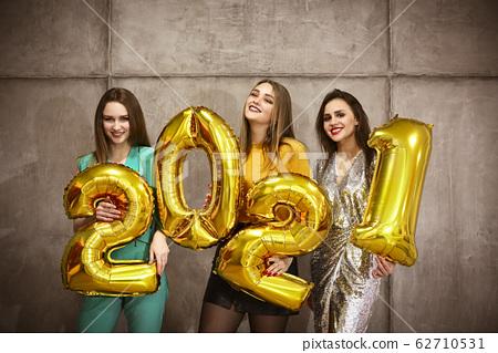 Stylish women holding golden balloons 2021 62710531