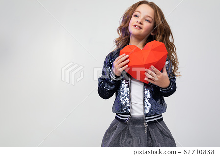 close-up of a happy stylish caucasian girl holding a red paper heart for valentines day on a white 62710838