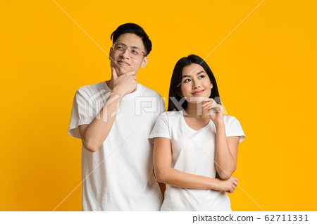 Young asian couple day dreaming on yellow background 62711331