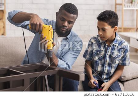 Afro Dad Teaching Preschool Son To Use Electric Drill At Home 62711616