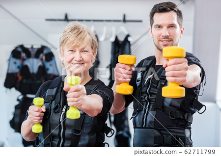 Fit senior lady and young man in ems gym 62711799