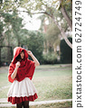 Portrait young woman with Little Red Riding Hood costume in green tree park 62724749