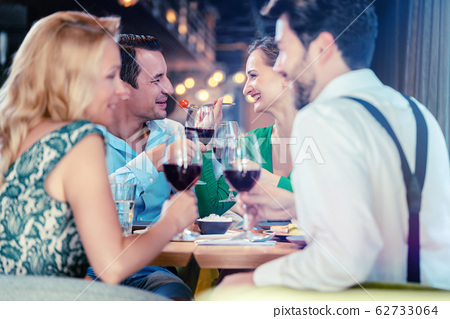 People in a restaurant eating and drinking red wine 62733064