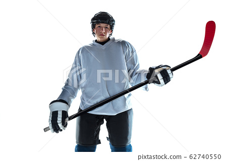 Young male hockey player with the stick on ice court and white background 62740550