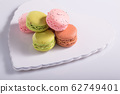 Two pink macaroons with poppy seeds on a 62749401