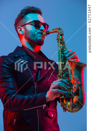 Young caucasian jazz musician playing the saxophone in neon light 62751647