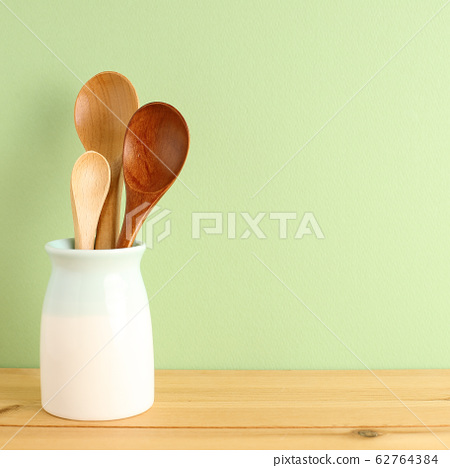 Wooden spoons in holder on wooden table with green background 62764384