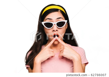 Young beautiful asian woman,long black hair Wearing a pink t-shirt, White fashion glasses, Yellow hair band smiling and Surprised isolated on white background 62786007