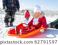 Winter activities for children. A little girl in a red coat sits on an orange sled before descending from a snow slide. Behind her are other children and a school in the distance. Snowy weather 62791597