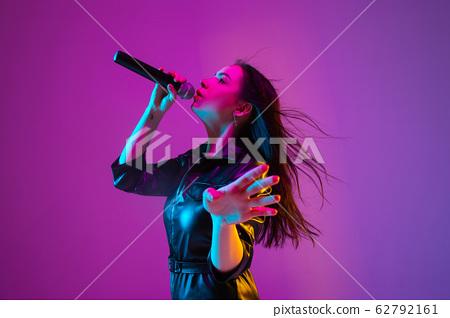 Caucasian female singer portrait isolated on purple studio background in neon light 62792161