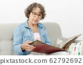 middle-aged woman looking at photo album 62792692