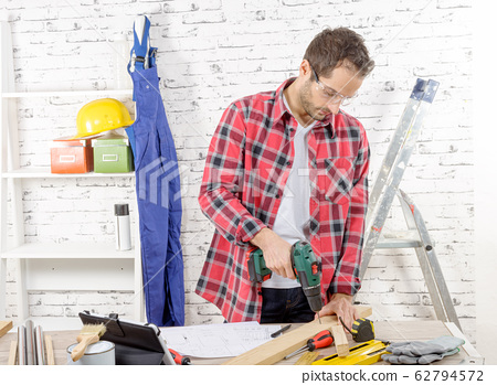 Carpenter drilling hole in plank, in his workshop 62794572