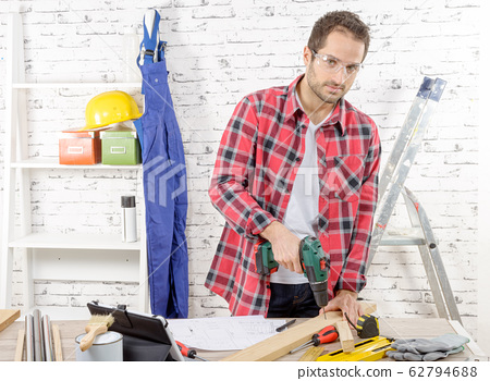 Carpenter drilling hole in plank, in his workshop 62794688