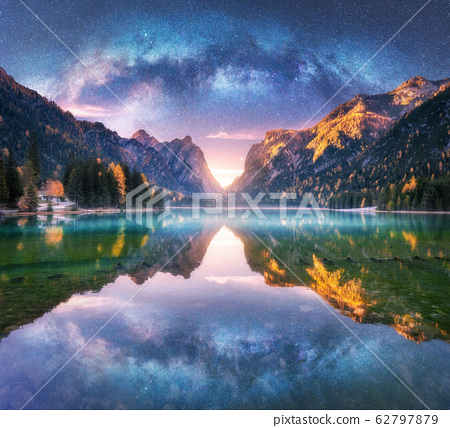 Milky Way reflected in water in mountain lake at starry night. Landscape with purple sky with stars 62797879