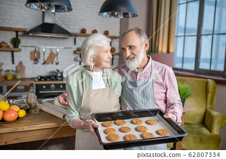 Couple of seniors holding just baked cookies 62807334