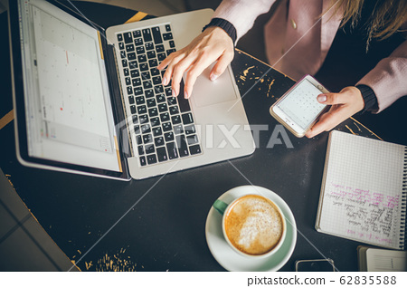 Close-up top view of Caucasian woman's hands Casually dressed student, blogger, writer man working on a laptop holding a phone in his hand, inside the cafe a wooden table and a cup of coffee 62835588