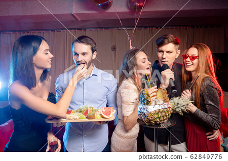 group of young people singing into microphone at party,celebrating birthday, karaoke 62849776