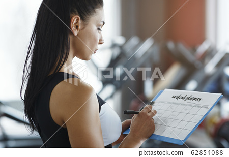 Personal trainer with clipboard making workout plan in gym 62854088