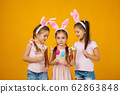 child girls holding painted Easter eggs 62863848