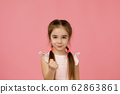 angry little child girl in dress raising fist 62863861