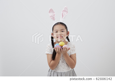 little child girl with easter bunny ears holding 62886142
