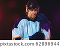 Male hockey player with the stick on ice court and dark neon colored background 62896944