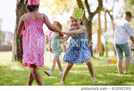 Small children standing outdoors in garden in summer, playing. 62898769