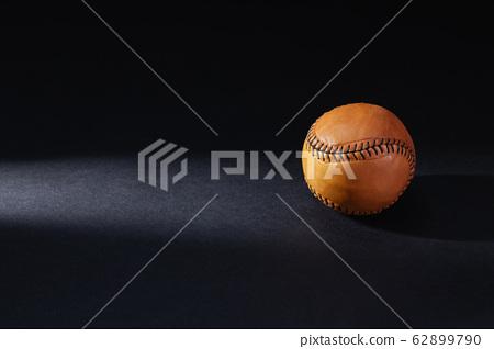 Brown baseball ball ion the black background. 62899790