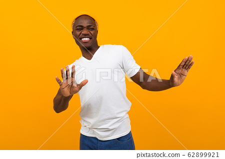 handsome smiling african man in a white t-shirt waving his arms and dancing on an orange background 62899921