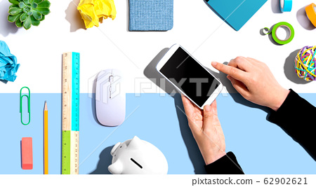Office supplies with person using a smartphone 62902621