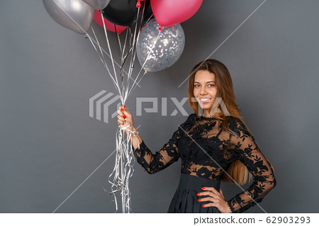 Young woman in black dress studio isolated on gray holding balloons 62903293