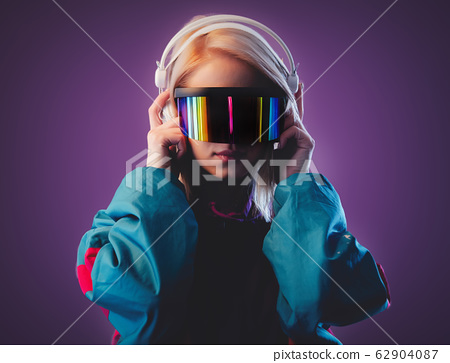 Blonde in VR glasses and headphones on pink 62904087