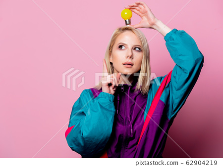 Blonde woman in 90s sport suit with bulb on pink 62904219