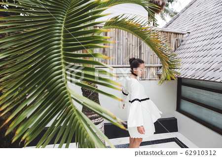Woman in white tunic in tropical garden with palm tree and white background 62910312