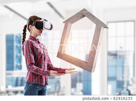 Girl in virtual reality mask experiencing virtual technology wor 62916235