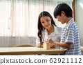Asian mother and son putting coins into bank home 62921112