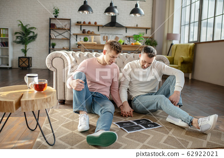 Two men sitting on the floor hand in hand. 62922021