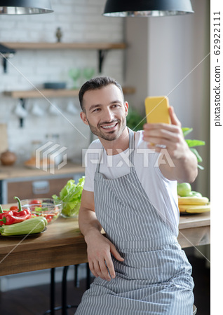 Young guy in an apron taking a selfie in the kitchen. 62922111