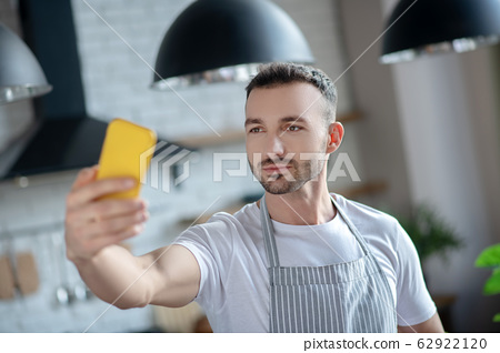 Young man with a yellow smartphone in his hand. 62922120