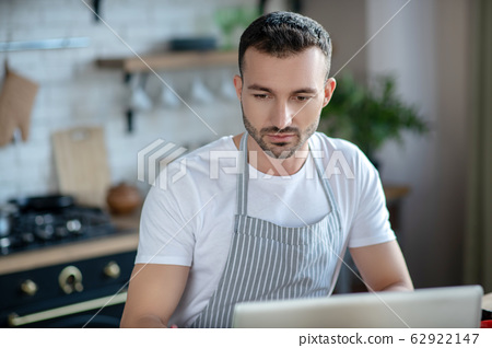 Successful young man in apron looking at laptop screen. 62922147