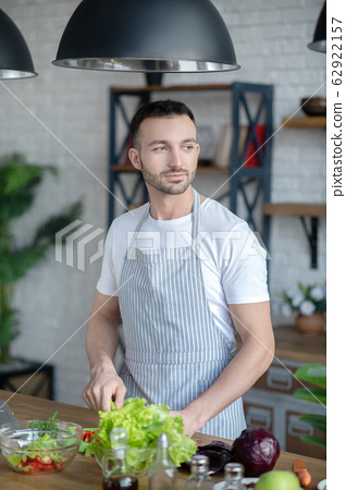 Dark-haired man in a kitchen apron cooking at home. 62922157