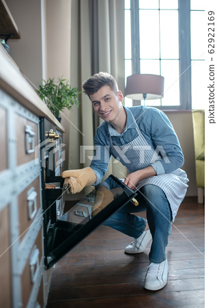 Smiling young guy taking out a baking sheet from the oven. 62922169