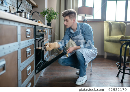Young man crouching near the oven taking out a baking tray. 62922170