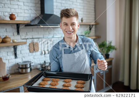 Young man with baking sheet of home baking in hands. 62922171