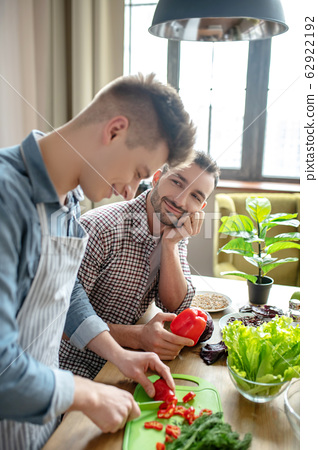 Male couple in the kitchen preparing their own food. 62922192