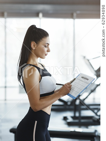 Personal trainer with clipboard building workout schedule for client in gym 62934898
